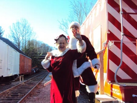 Mr. and Mrs. Claus wave at all the boys and girls on the Jingle bell trolley train.